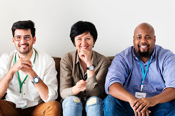 Three people smiling and sitting on a couch.